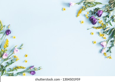 Flowers composition. Yellow and purple flowers on pastel blue background. Spring, easter concept. Flat lay, top view, copy space