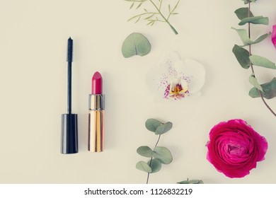 Flowers and cosmetic composition - dried eucaliptus leaves and flowers on white background. Flat lay scene with copy space, retro toned