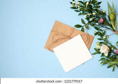 Flowers, craft envelopeь, blank letter on blue background with copy space for your text. Mockup for banner, greeting card. Woman's day, 8 march, wedding, dating, love concept. Flat lay, top view.