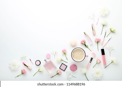 Flowers with cup of coffee and makeup cosmetics on white background