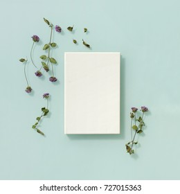 Flowers decorated around a book on light turquoise background