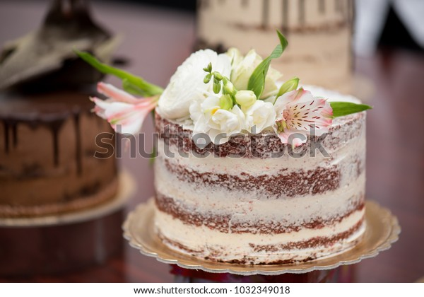 Flowers decorated red sponge cake with vanilla cream on a glass plate