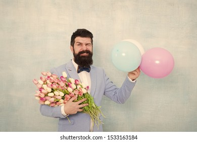 Flowers delivery. Gentleman romantic date. Birthday greetings. Confidence and charisma. Man bearded gentleman suit bow tie hold air balloons and bouquet. Gentleman making romantic surprise for her.