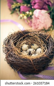 Flowers and easter nest with eggs on rustic wooden background. Spring time. Retro toned
