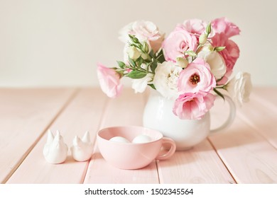 flowers with eggs for easter on pink wooden background