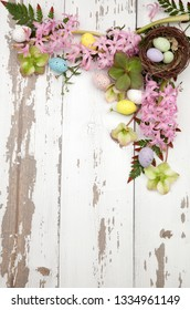 Flowers and eggs frame over rustic wooden boards, background for Easter. Copy space.