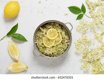 Flowers of the elder and lemon slices in a cooking pot for making elderflower syrup. Top view.