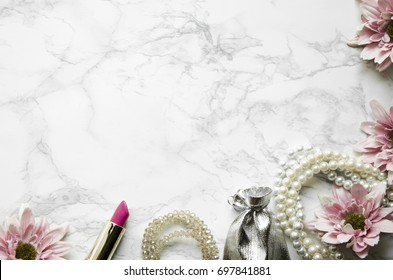 Flowers with feminine accessories lie on a marble background
