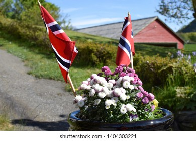 Flowers and flags. Street of the Norwegian village on the eve of the celebration of the Norwegian Constitution Day.