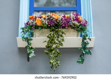 Flowers in flowerpot (fake flowers) and blue window on grey wall of a house.