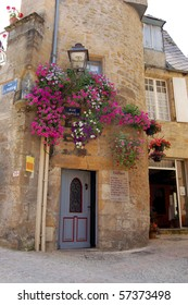 Flowers frame the door of a hairdressers shop in Sarlat