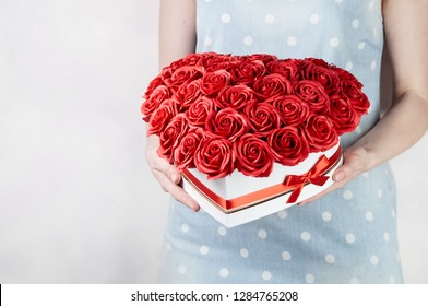 Flowers as a gift: A girl is holding a large bouquet of red roses in a white box on a white background.