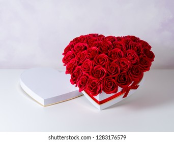 Flowers as a gift: A large bouquet of red roses in a white box with a red ribbon on a white background.