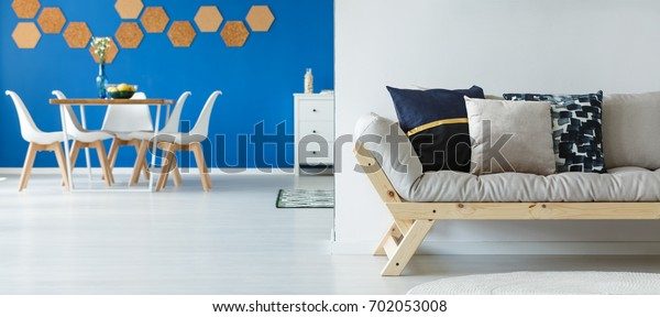 Flowers in glass vase on small dining table with white chairs in spacious room with blue wall
