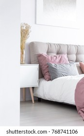Flowers in glass vase on white cupboard next to king-size bed in bright modern flat interior with gray bedhead and pink accent