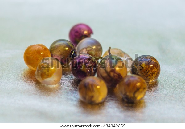 Flowers and glitters inside of ball shaped crystals made of epoxy resin close-up with bokeh on toned background shallow depth of field