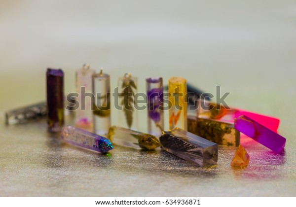 Flowers and glitters inside of crystals made of epoxy resin close-up with bokeh on toned background shallow depth of field