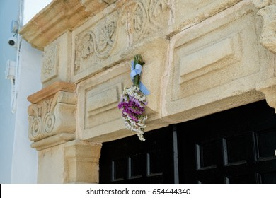 Flowers hanged over a traditional doorway as a symbol of May Day celebrations (spring festival) in the Greek Village of Lindos. Island of Rhodes, Greece.