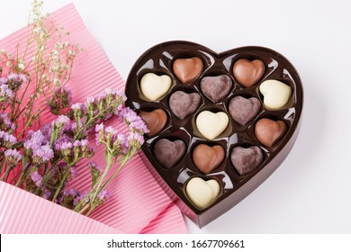 Flowers with heart shaped box of chocolates on white background