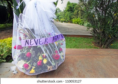 "Flowers and an important message (""Never Again"") placed on top of the mass graves and tombs of 500,000 murdered tutsi tribespeople at the Rwandan Genocide Memorial in Kigali, Rwanda."