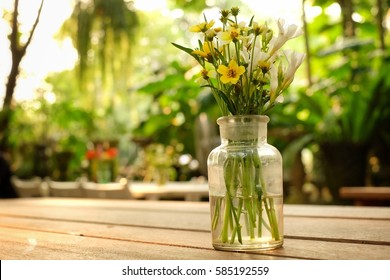 Flowers jar on the table blur background