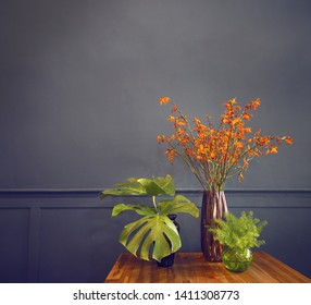 flowers and leafs in glass vase, darkblue wall