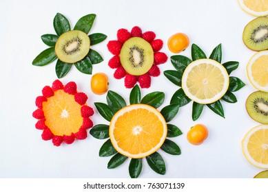 Flowers made of citrus fruits isolated on white. Orange, lemon, kiwi, tangerine and raspberry. Colorful and fresh composition.