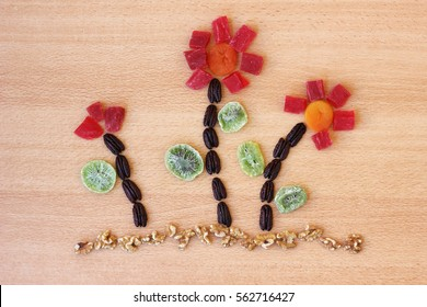 Flowers made of dried fruits and almonds on wooden background - symbols of judaic holiday Tu Bishvat.