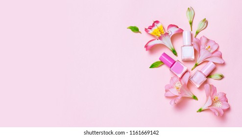 Flowers and nail poloshes composition on pink table. Beauty and manicure concept. Top view, flat lay. Copyspace for text or logo