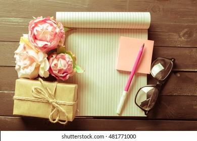 flowers and a notebook on wooden background
