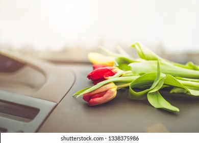 Flowers on the dashboard in the car - a gift to the girl