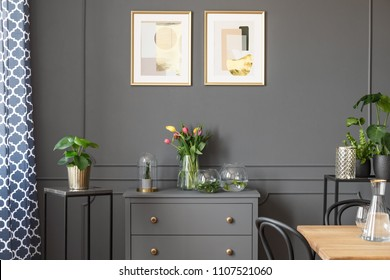 Flowers on grey cabinet under posters in minimal loft interior with plants. Real photo