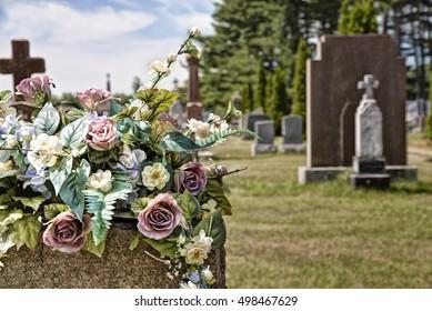 Flowers on a headstones in a cemetery, bokeh effect in background.