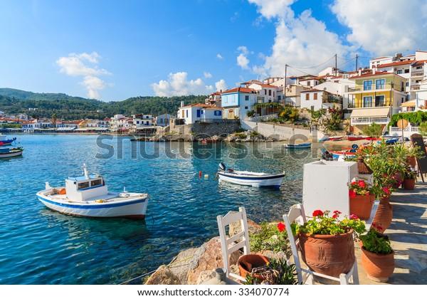 Blumen an Land mit Fischerbooten im Hafen Kokkari, Insel Samos, Griechenland