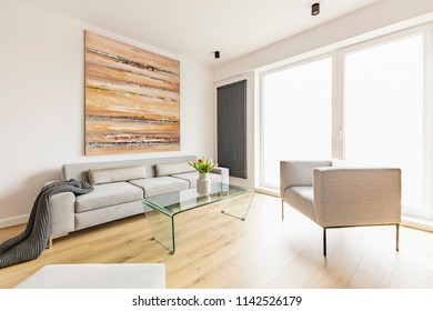 Flowers on table between couch with blanket and armchair in apartment interior with painting. Real photo