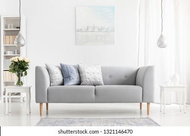 Flowers on table next to grey settee with pillows in apartment interior with poster and lamps. Real photo
