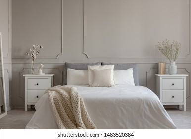 Flowers on white wooden nightstand table in luxury bedroom interior with king size bed
