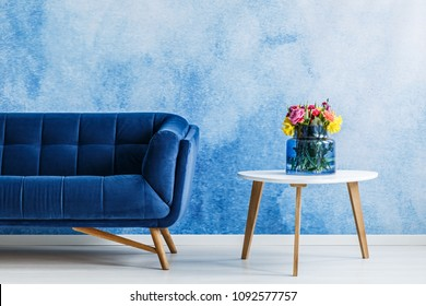 Flowers on white wooden table next to navy blue suede couch in elegant living room interior