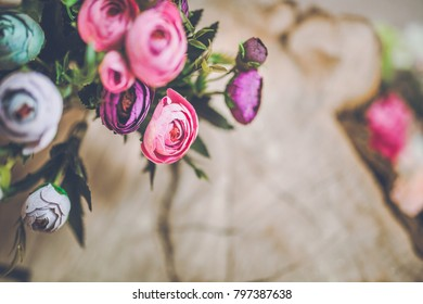 flowers on wood background with coffee and cookies