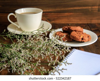 Flowers on wooden floor with coffee and chocolate cookies use for background with copy space