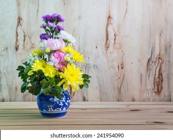 flowers on wooden table over grunge background