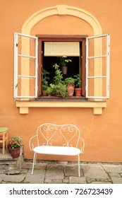 Flowers in the open window with bench of the historic house in Old Town in Cesky Krumlov, Czechia, Heritage Unesco.