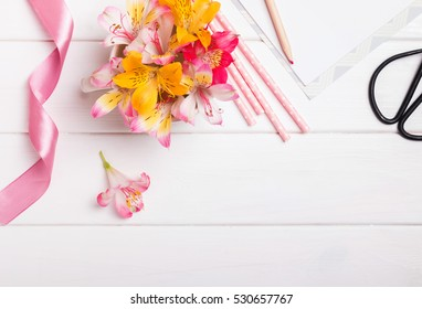Flowers, paper straws and pink ribbon on white wooden table, top view