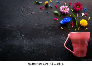 flowers, petals and herbs from a pink mug on a black background with space for text