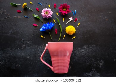 flowers, petals and herbs from a pink mug on a black background
