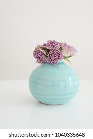 Flowers pink dry roses in a round turquoise vase