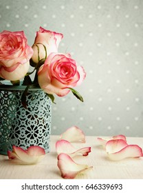 Flowers pink roses in a vase on vintage background wall.
