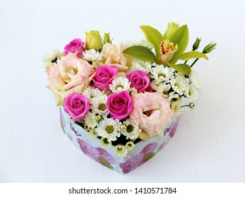 flowers pink roses, white chrysanthemums, green Orchid, pink eustoma in a heart-shaped box, top view on a white wooden table with a blurred background