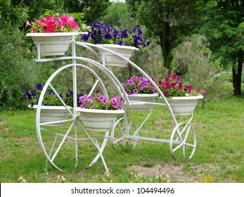 Flowers in pots on flowerbed in garden