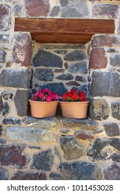 Flowers in Pots in a Stone Wall